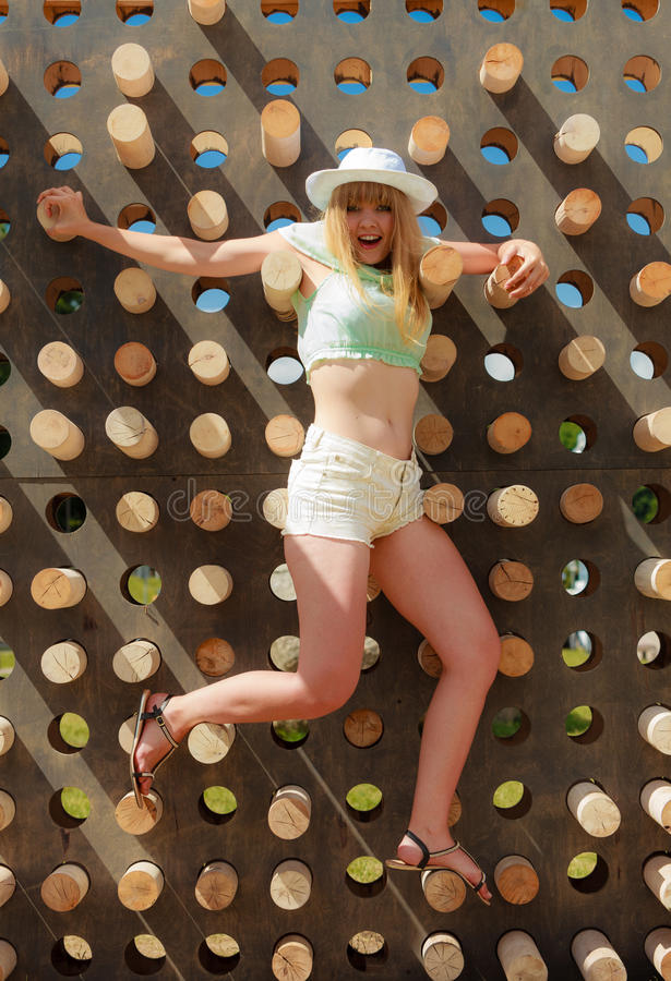 Den lyckliga unga blonda kvinnan som klättrar upp i affärsföretag, parkerar arkivfoto