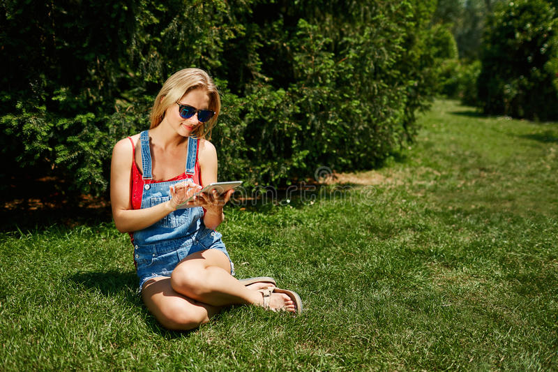 Den lyckliga unga blondy PC:n för minnestavla för kvinnahögskolestudentbruk sitter på gr arkivbilder
