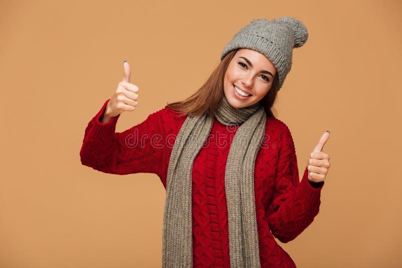 Den lyckliga unga brunettkvinnan i stucken klädervisning tummar upp ges arkivbild