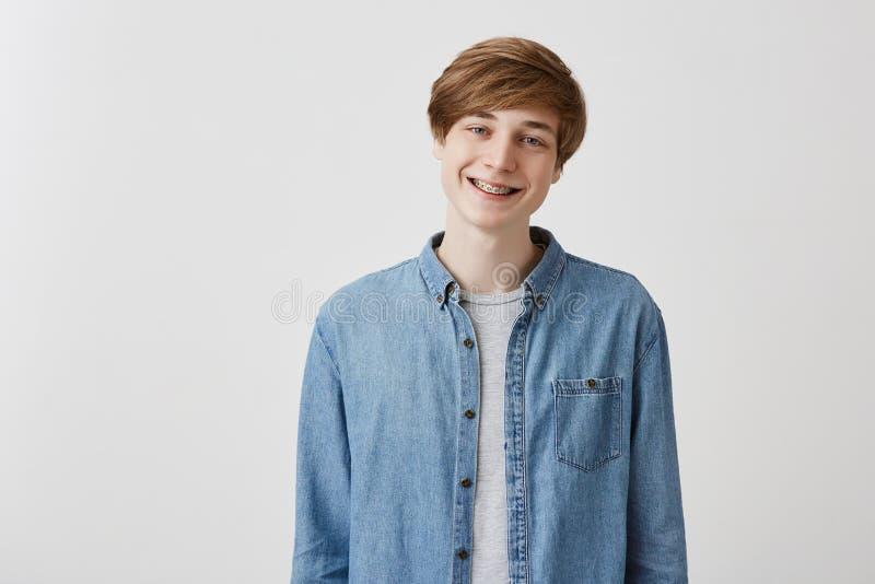 Den lyckliga unga europeiska mannen med ganska hår och blåa ögon, leenden i huvudsak med hänglsen, jublar för att möta vänner, ha royaltyfria foton