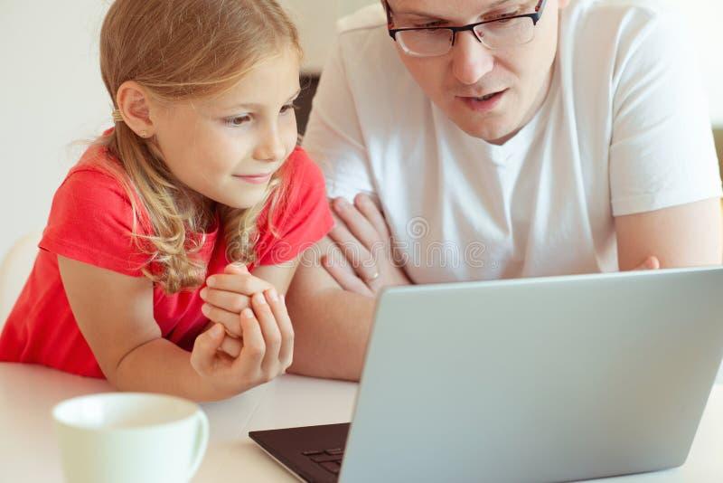 Den lyckliga unga fadern har gyckel med hans nätta dotter under arbete arkivbild