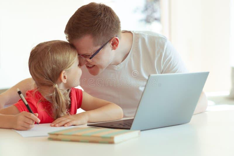 Den lyckliga unga fadern har gyckel med hans nätta dotter under arbete arkivfoton