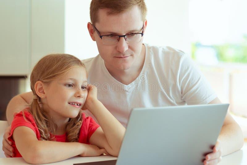 Den lyckliga unga fadern har gyckel med hans nätta dotter under arbete royaltyfri fotografi