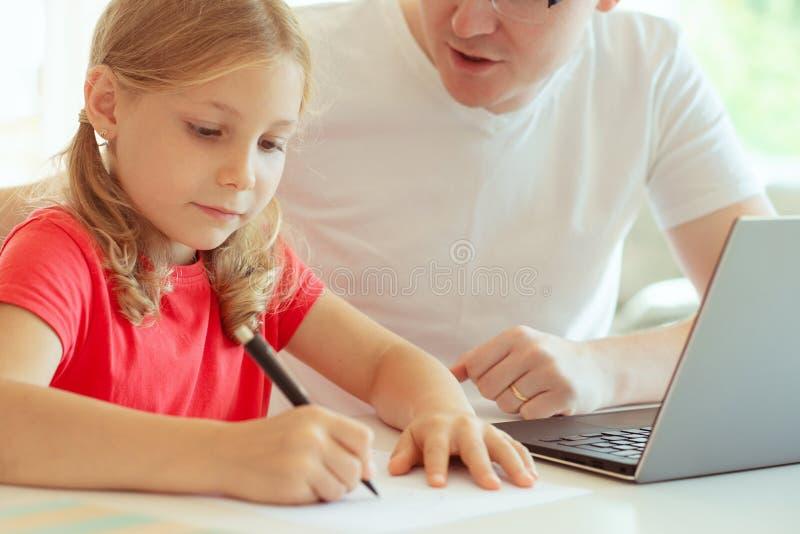 Den lyckliga unga fadern har gyckel med hans nätta dotter under arbete royaltyfri bild
