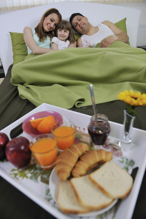 Den lyckliga unga familjen äter frukosten i underlag fotografering för bildbyråer