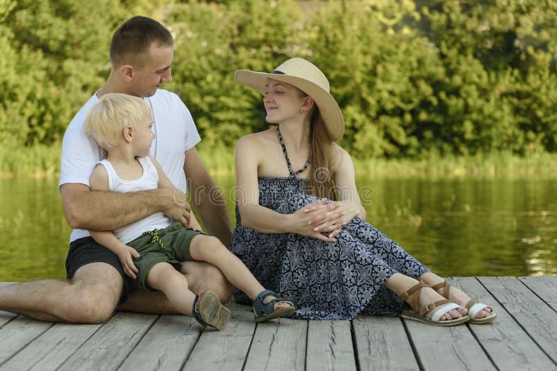Den lyckliga unga familjen, fadermodern och den lilla blonda sonen sitter på flodpir fotografering för bildbyråer