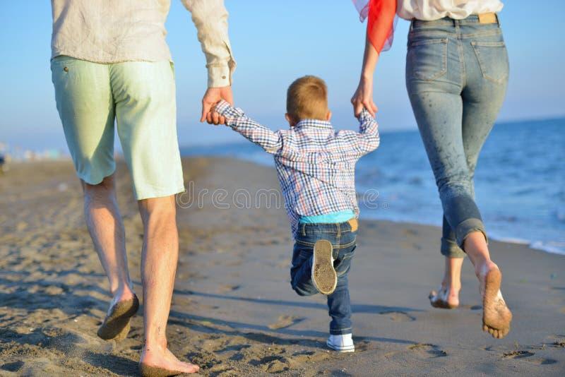 Den lyckliga unga familjen har gyckel på den körda stranden och hoppar på solnedgången royaltyfria bilder