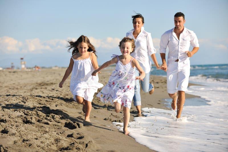 Den lyckliga unga familjen har gyckel på strand royaltyfria foton