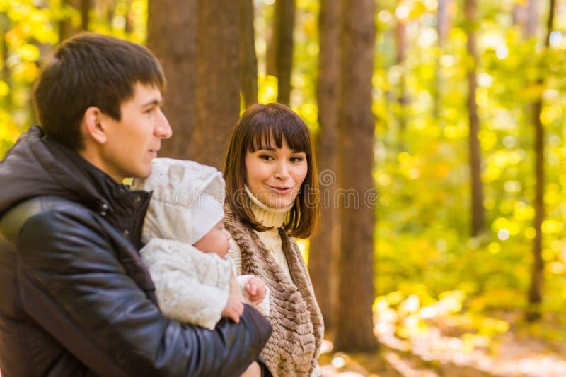 Den lyckliga unga familjen i hösten parkerar utomhus på en solig dag Modern, fadern och deras små behandla som ett barn pojken gå royaltyfri fotografi