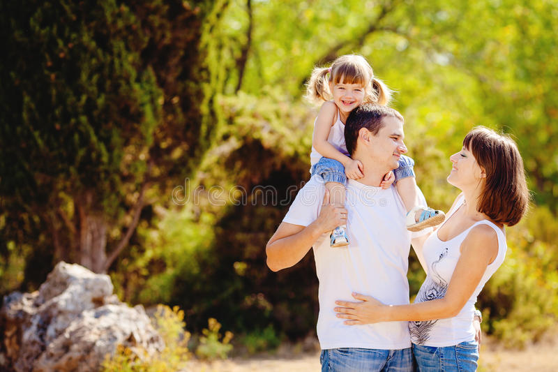 Den lyckliga unga familjen med barnet som utomhus vilar i sommar, parkerar royaltyfri foto