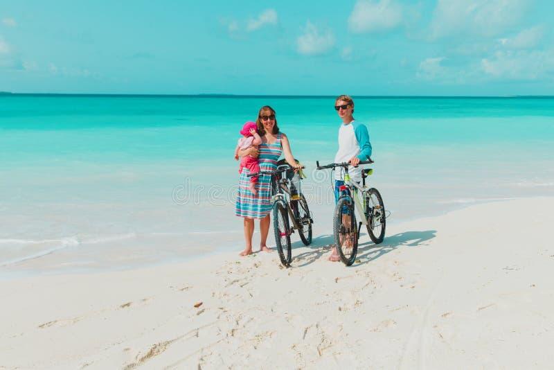 Den lyckliga unga familjen med behandla som ett barn rida cyklar på stranden royaltyfri fotografi
