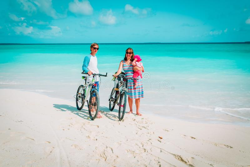 Den lyckliga unga familjen med behandla som ett barn rida cyklar på stranden arkivfoton