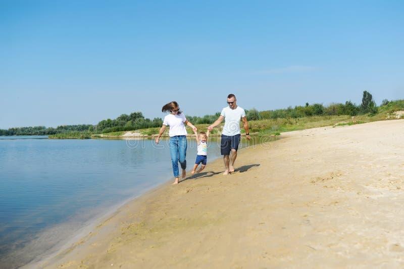 Den lyckliga unga familjen med deras lilla son spenderar tid tillsammans på naturen arkivfoton