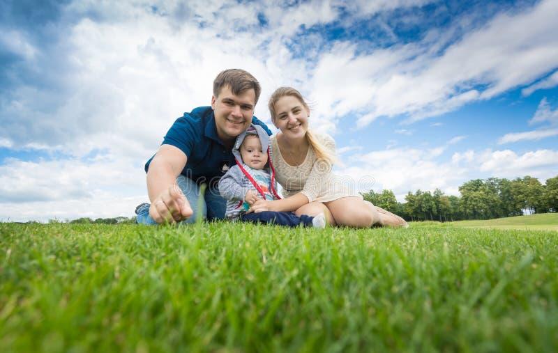 Den lyckliga unga familjen med 9 gamla månader behandla som ett barn pojken som kopplar av på gräs royaltyfri fotografi