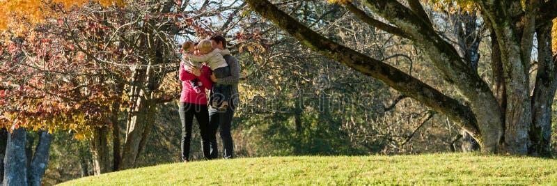 Den lyckliga unga familjen med två ungar i parkerar royaltyfria foton