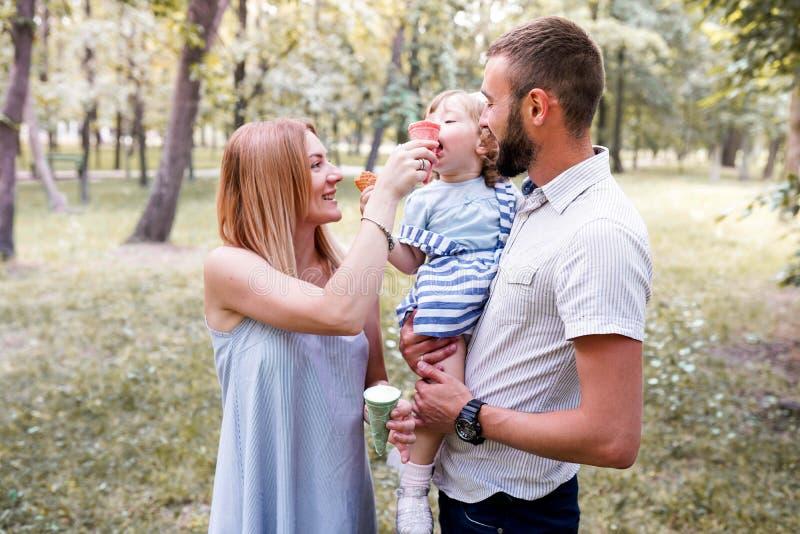 Den lyckliga unga familjen som äter glass som spenderar tid som är utvändig i grön natur, parkerar tillsammans royaltyfri foto