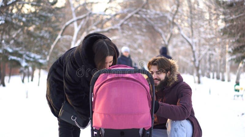 Den lyckliga unga familjen som går i en vinter, parkerar, mamman, farsa och behandla som ett barn i sittvagn Le föräldrar som lut arkivbilder