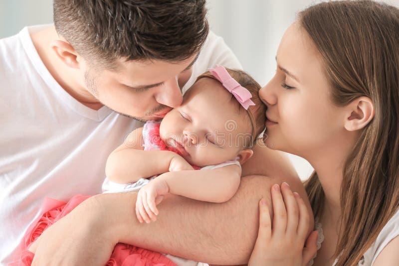 Den lyckliga unga familjen som rymmer gulligt sova nyfött, behandla som ett barn royaltyfri foto