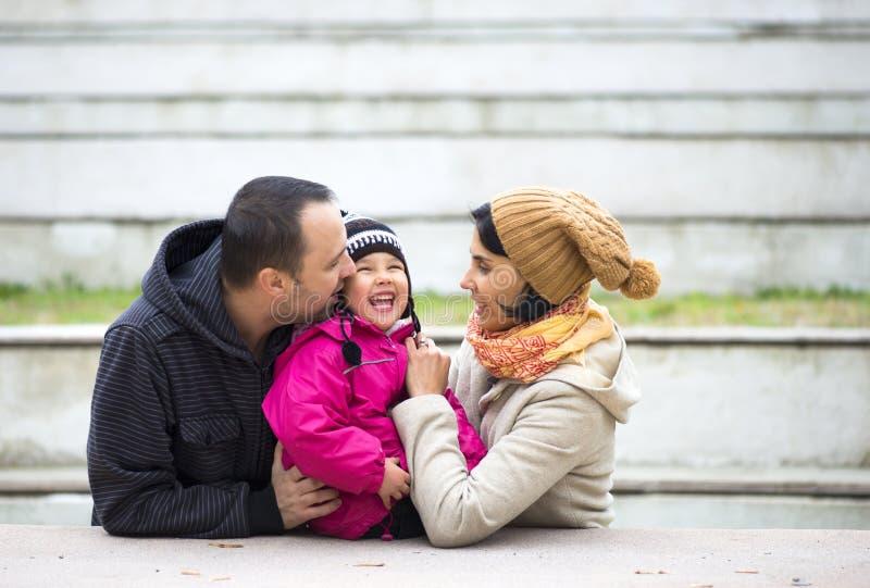 Den lyckliga unga familjen som spenderar tid parkerar in royaltyfria foton