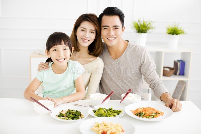 Den lyckliga unga familjen tycker om deras matställe royaltyfri bild