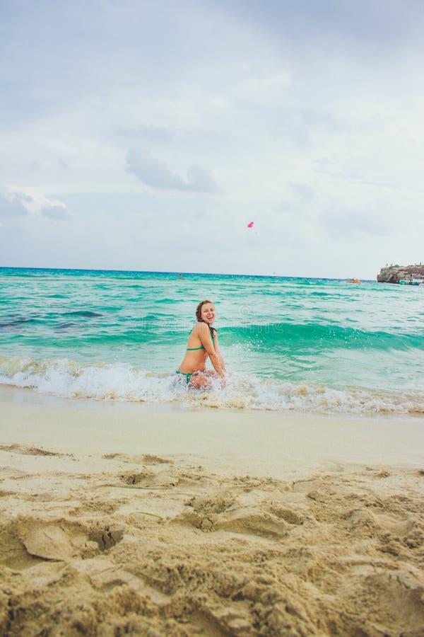 Den lyckliga unga flickan i sprejen av havet vinkar arkivfoto