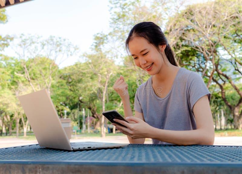 Den lyckliga unga flickan med en telefon i hennes händer som arbetar på en bärbar dator på tabellen i, parkerar Begreppet av att  royaltyfria bilder