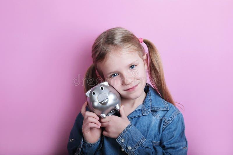 Den lyckliga unga flickan med försilvrar spargrisen på rosa bakgrund begreppspengar sparar royaltyfri fotografi