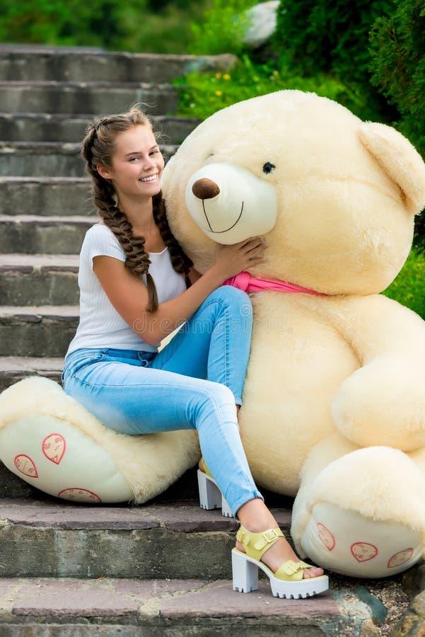 Den lyckliga unga flickan på trappan i parkera kramar hennes enorma nalle b arkivbilder