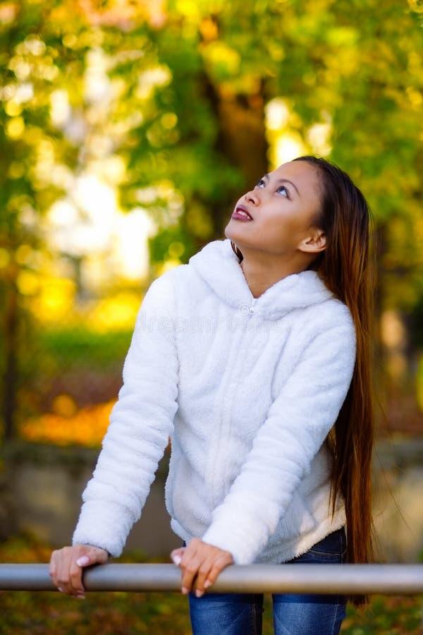 Den lyckliga unga härliga kvinnan i höst parkerar på den soliga dagen, ung kvinna i det vita laget under solnedgång i parkera fotografering för bildbyråer