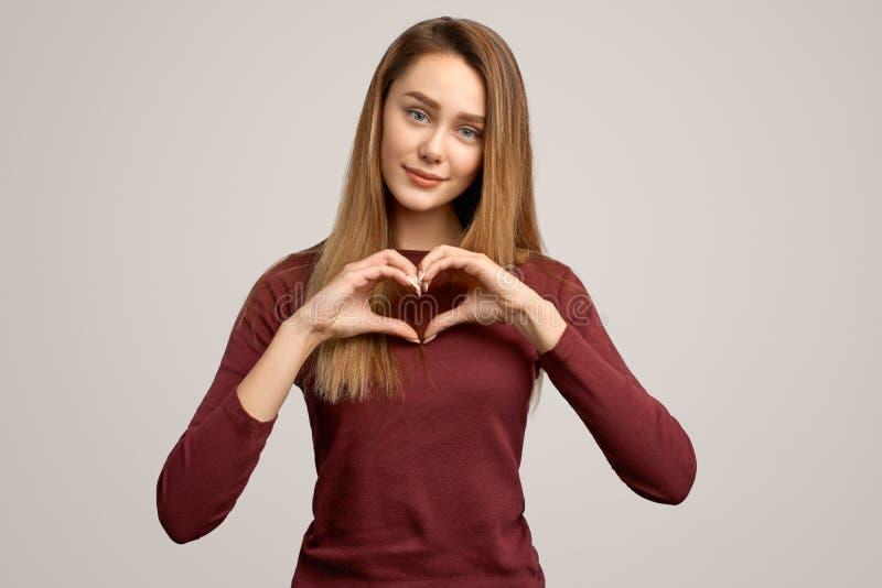 Den lyckliga unga härliga kvinnan visar bröstkorgen för hjärtatecknet över, visar affektion, förälskelse och fred Kroppsspråkbegr arkivfoton