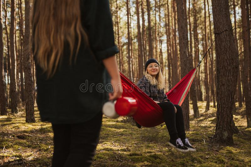 Den lyckliga unga hipsterflickan tycker om liv och naturen på hängmattan med annan kvinna i sommarskogen arkivfoton