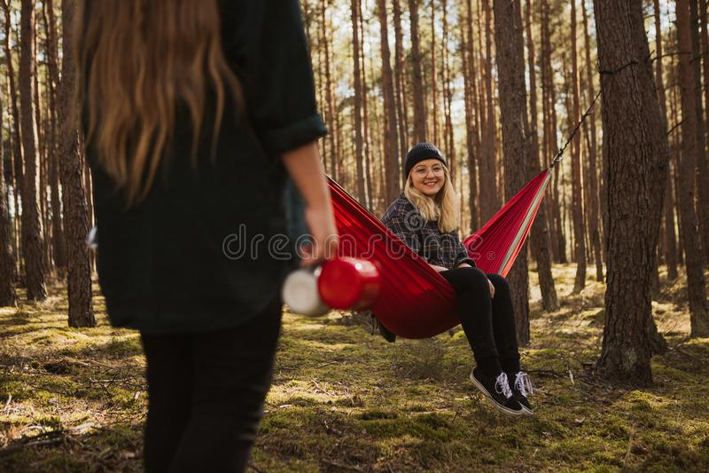 Den lyckliga unga hipsterflickan tycker om liv och naturen på hängmattan med annan kvinna i sommarskogen royaltyfria bilder