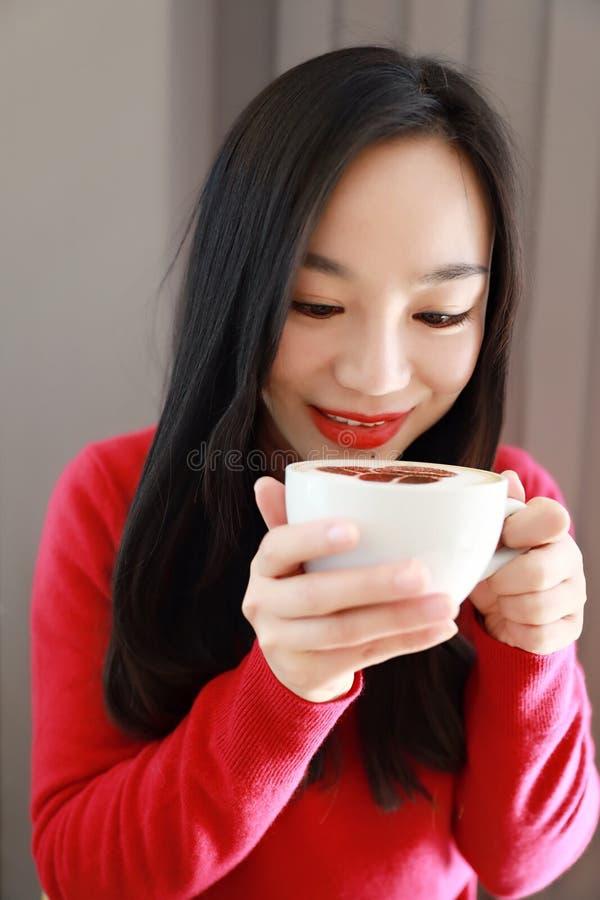 Den lyckliga unga kvinnan är under en filt och en kopp kaffe på vintermorgon hemma arkivfoton