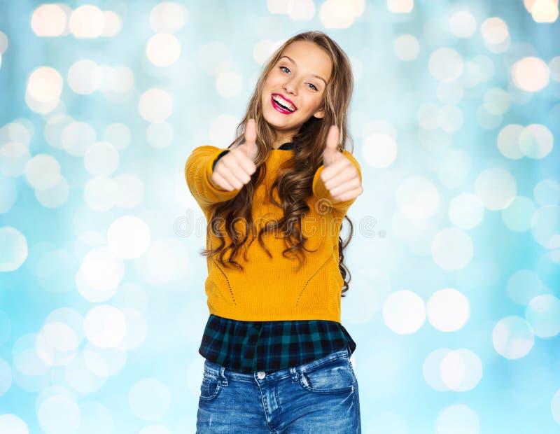 Den lyckliga unga kvinnan eller den tonåriga flickavisningen tummar upp arkivfoton