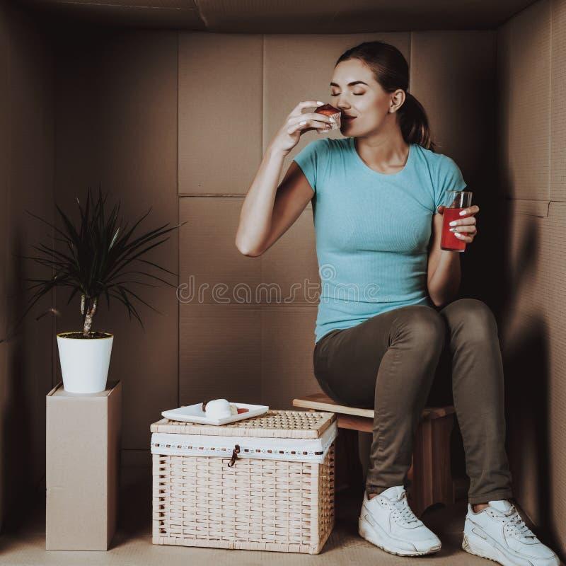 Den lyckliga unga kvinnan har lunch i kartong arkivbild