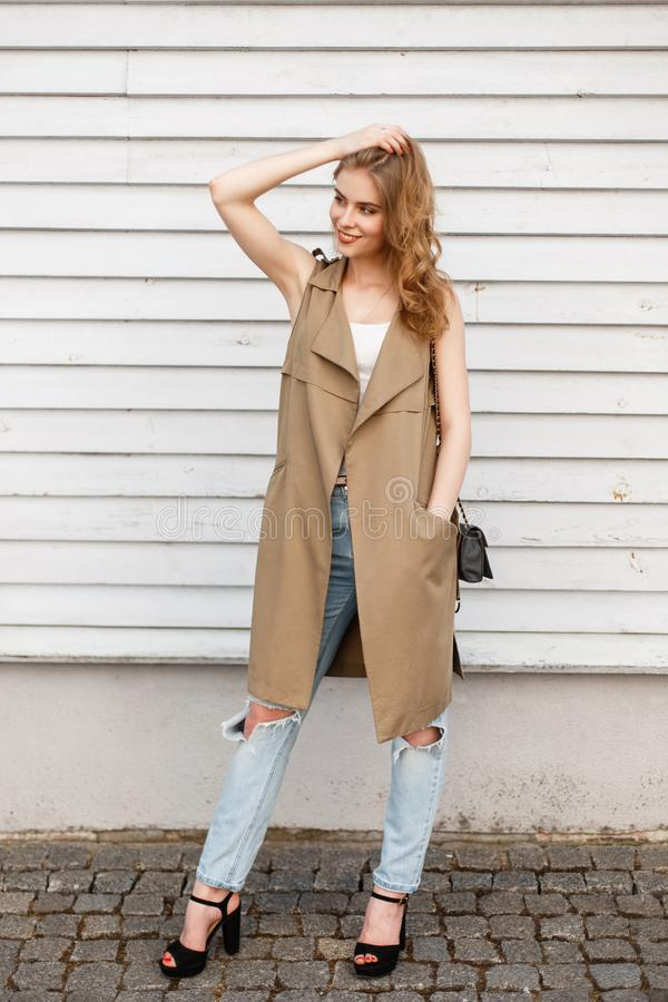 Den lyckliga unga kvinnan i en stilfull sommar tilldelar en vit T-tröja i trendig riven sönder jeans i svarta skor med en läderha royaltyfria foton