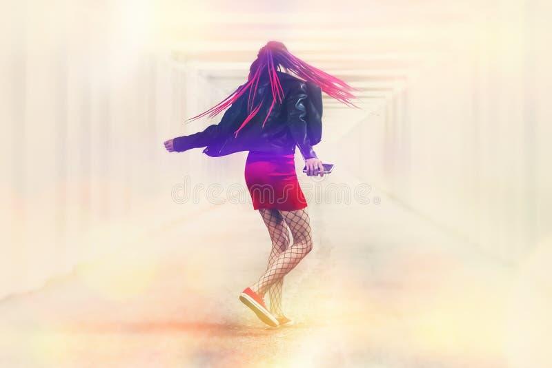 Den lyckliga unga kvinnan i hörlurar lyssnar till musik med den smarta telefonen som dansar Flicka med rosa råttsvansar som roter fotografering för bildbyråer