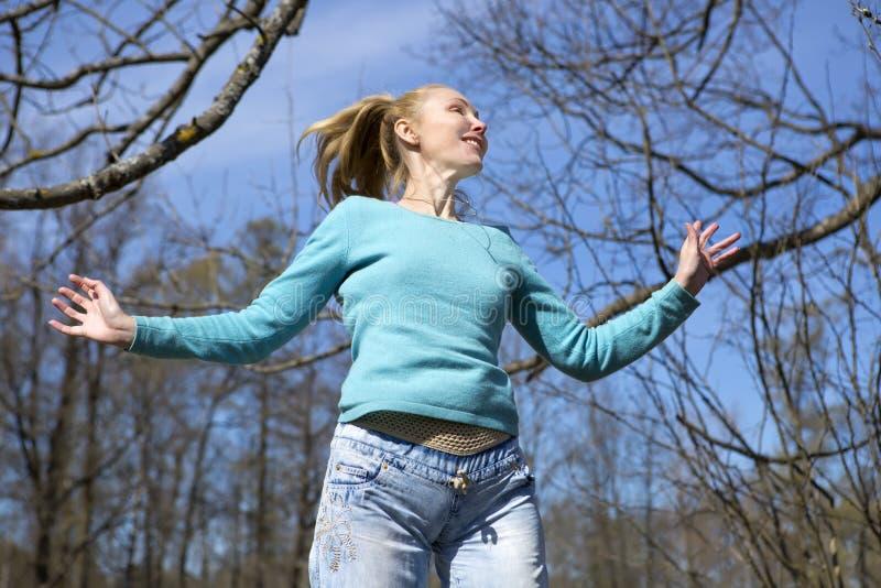 Den lyckliga unga kvinnan i ljus kläder hoppar i vår parkerar royaltyfri fotografi
