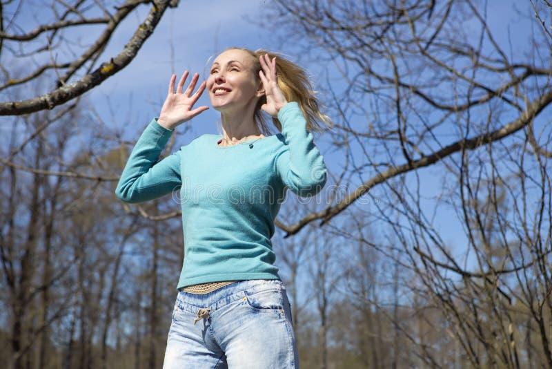Den lyckliga unga kvinnan i ljus kläder hoppar i vår parkerar arkivbild