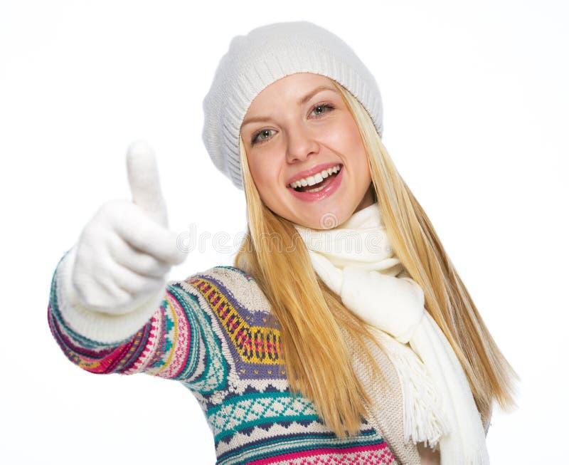 Den lyckliga unga kvinnan i vinter beklär upp visningtummar royaltyfria foton
