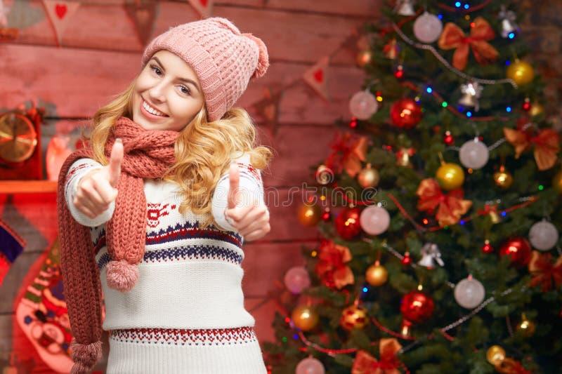 Den lyckliga unga kvinnan i vinterkläder visar upp tummen arkivfoton