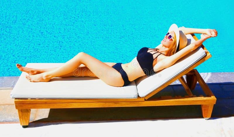 den lyckliga unga kvinnan ligger koppla av på deckchair över bakgrund för pöl för blått vatten arkivbilder