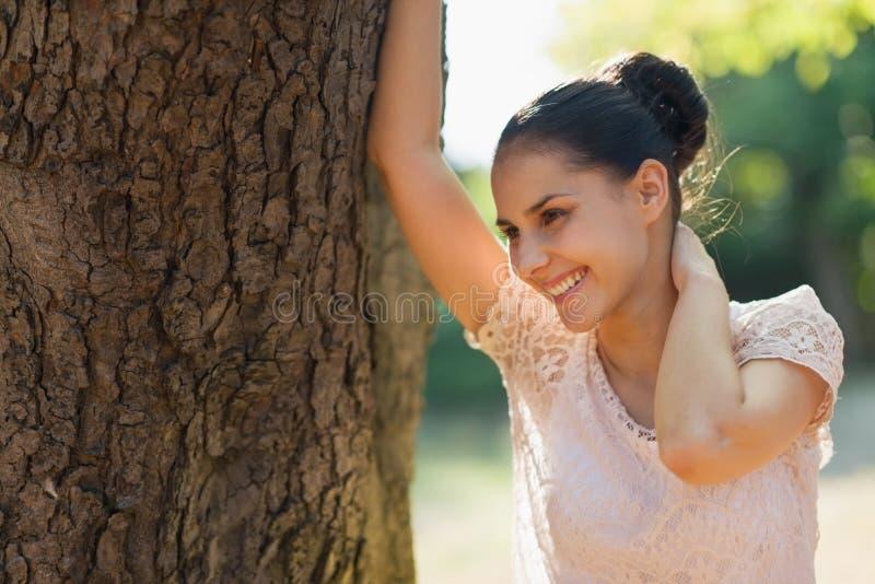 Den lyckliga unga kvinnan lutar mot tree royaltyfri bild