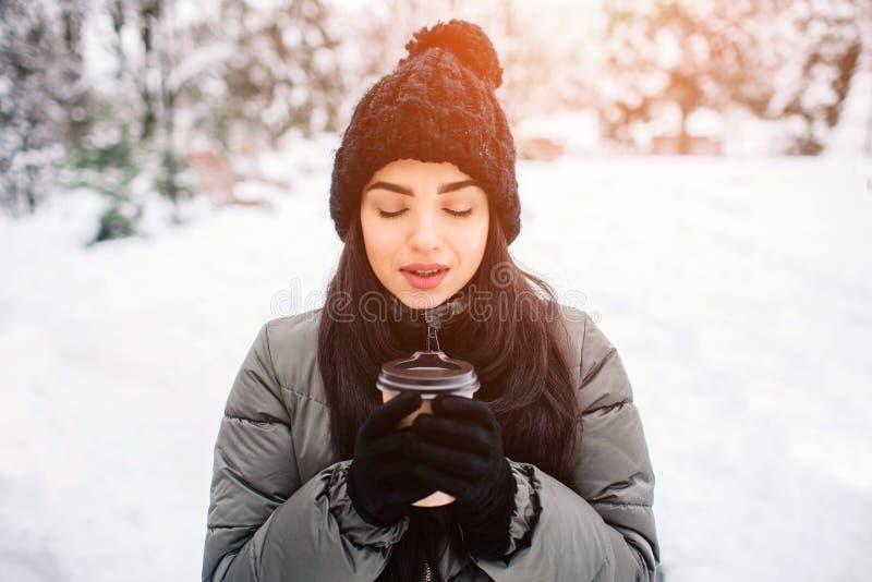 Den lyckliga unga kvinnan med en kopp av varmt te eller kaffe på snöig vinter går i natur Begrepp av frostvintersäsongen royaltyfri foto