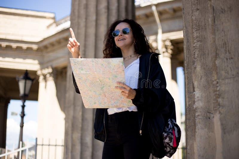 Den lyckliga unga kvinnan med en stadsöversikt i händer som visar upp ett finger, har en ryggsäck som ler, över domkyrkabakgrund royaltyfria bilder