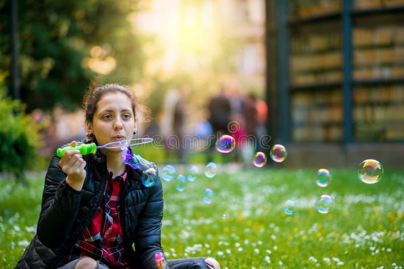 Den lyckliga unga kvinnan med härligt leende blåser bubblor fotografering för bildbyråer