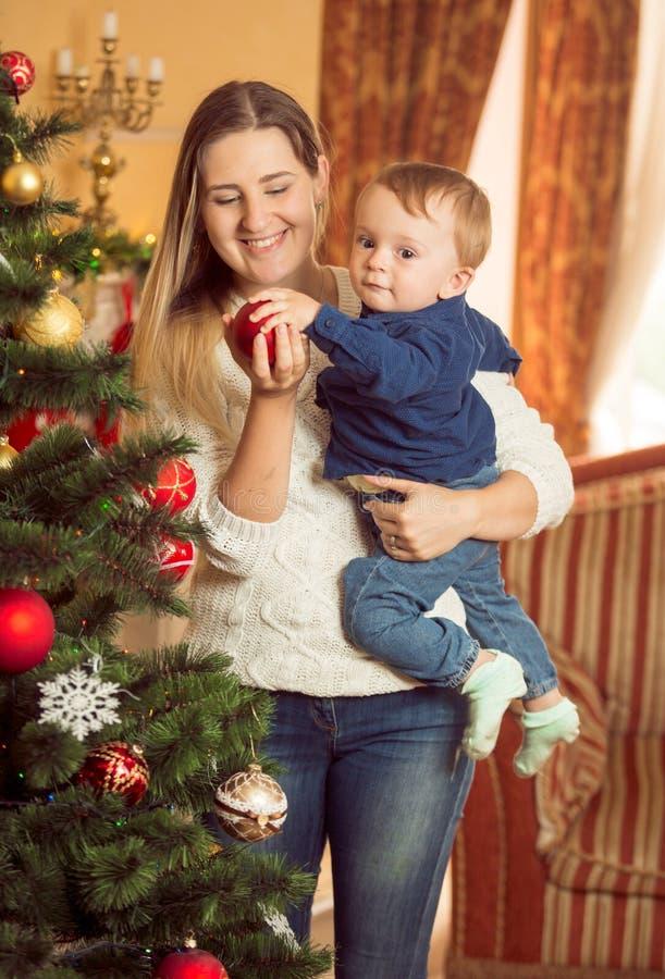Den lyckliga unga kvinnan med henne behandla som ett barn sonen som dekorerar julgranen royaltyfri fotografi