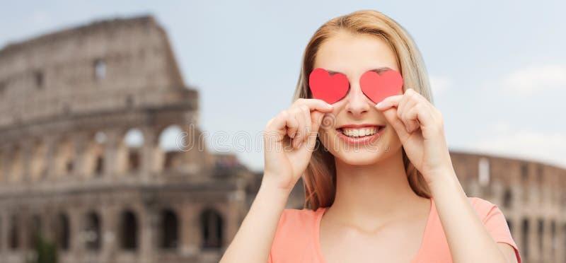 Den lyckliga unga kvinnan med röd hjärta formar på ögon arkivfoton