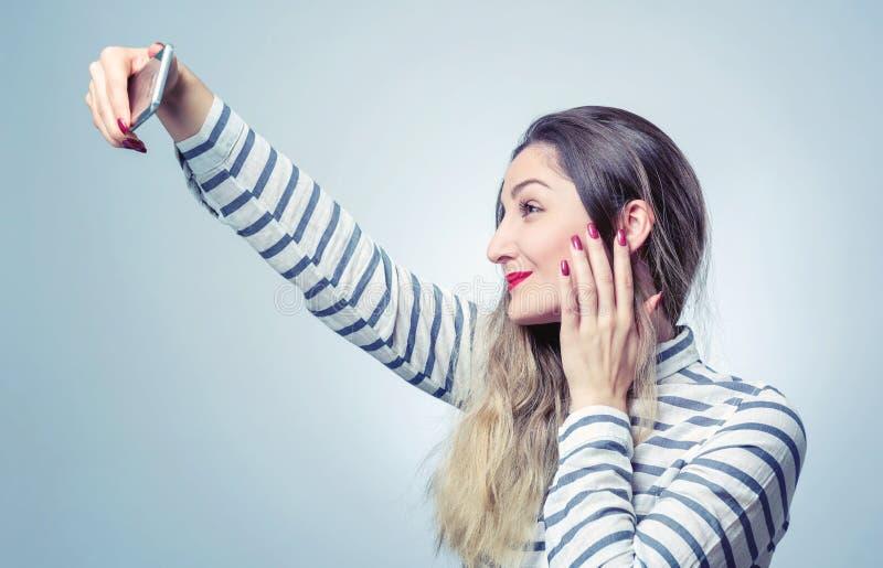 Den lyckliga unga kvinnan med smartphonen gör selfie på bakgrund arkivbilder