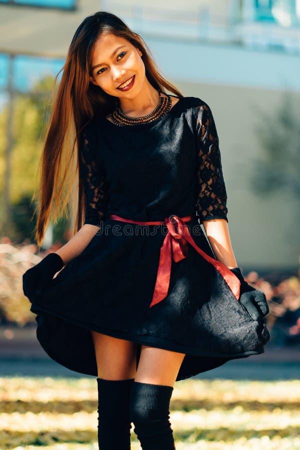 Den lyckliga unga kvinnan parkerar in på den soliga höstdagen som ler Gladlynt härlig flicka i svart retro stil för klänninghöstm arkivbilder